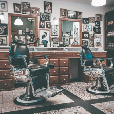 An old-school barber shop with mirrors, chairs, and photos.
