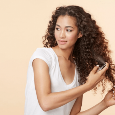 model with curly brown hair spraying in hair product