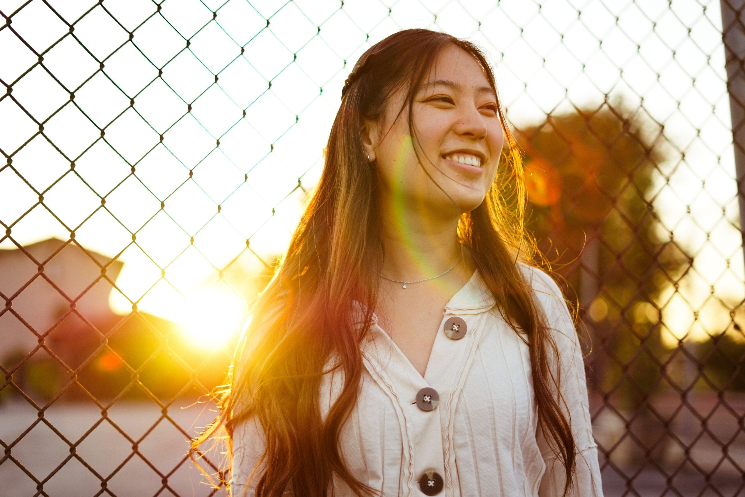 smiling woman leaning against a fence