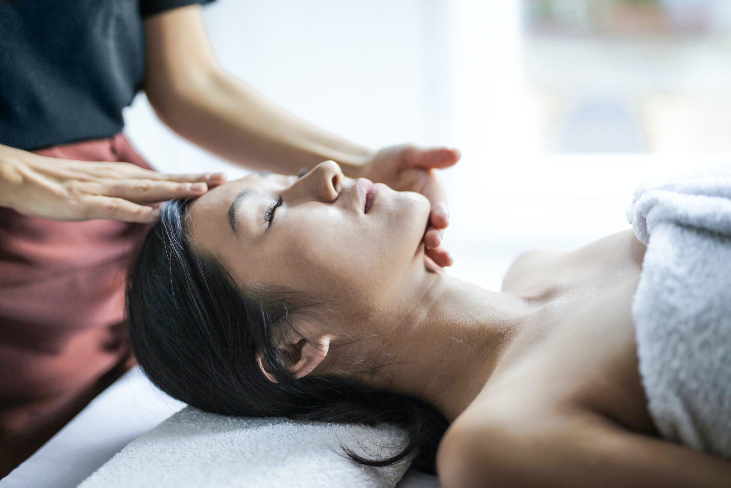 woman receiving facial massage at a spa
